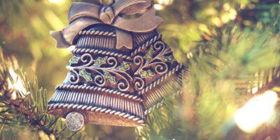 Ozdroba choinkowa w postaci podwójnego dzwoneczka w kokardką wisi na bożonarodzeniowym drzewku choinkowym