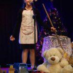 Solistka na scenie z miotłą w ręku. Za nią scenografia: choinka, fotel z pledem, stolik z koronkowym obrusem i zabawki dla dzieci. Foto Karolina Gera