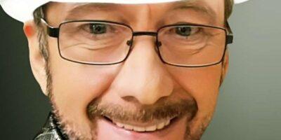 Uśmiechnięty mężczyzna w białym kapeluszu z wzorzystą przepaską. Na twarzy ma czarne okulary.