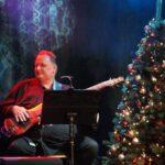 Basista Andrzej Rusek siedzący z gitarą na scenie SCK- Bytków. Obok choinka