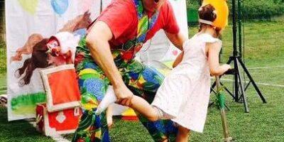 Na zdjęciu przebrany za kolrowego klauna aktor bawi się z dziećmi