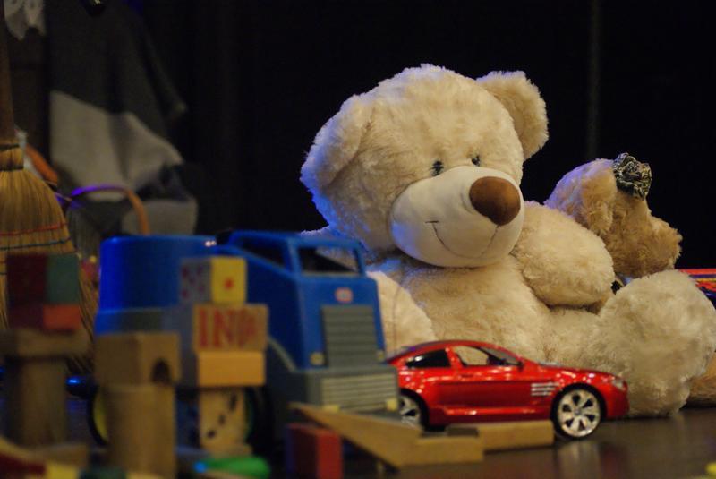 Dziecięce zabawki stanowiące scenografię koncertu: Miś, klocki i czerwony samochodzik