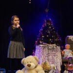 Solistka na scenie z mikrofonem w ręku. Za nią scenografia: choinka, fotel z pledem, stolik z koronkowym obrusem i zabawki dla dzieci. Foto Karolina Gera