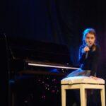 Wokalistka siedzi na białym krzesełku przy czarnym pianinie, na scenie. Foto Karolina Gera