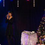 Solistka na scenie w czarnej sukience. Za nią scenografia: choinka, fotel z pledem, stolik z koronkowym obrusem i zabawki dla dzieci. Foto Karolina Gera