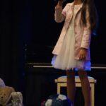 Wokalistka w białej sukience stoi na scenie z mikrofonwm w ręku. Przed nią leżą zabawki. W tle czarne pianino. Foto Karolina Gera