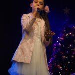 Wokalistka w białej, tiulowej sukience stoi na scenie z mikrofonem w dłoni. Za nią choinka. Foto Karolina Gera