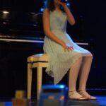 Wokalistka w jasno błękitnej sukience siedzi z mikrofonem w ręku na białym taborecie przy czarnym pianinie. Foto Karolina Gera