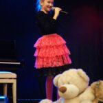 Wokalistka w czarnej bluzce i czerwonej sukience stoi na scenie z mikrofonem w ręce. Jako element dekoracji na scenie leży miś. Foto Karolina Gera