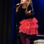 Wokalistka w czarnej bluzce i czerwonej sukience stoi na scenie z mikrofonem w ręce. Foto Karolina Gera