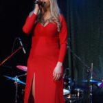 Daria Wantuła w czerwonej, długiej sukni śpiewa do mikrofonu na scenie SCK- Bytków