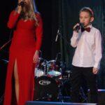 Daria Wantuła w długiej, czerwonej sukni oraz Szymon Wantuła z mikrofonami w rękach na scenie SCK- Bytków