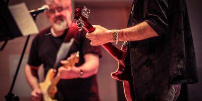 Dwóch mężczyzn grających na gitarach elektrycznych. Mężczyzna na pierwszym planie ubrany na czarno.