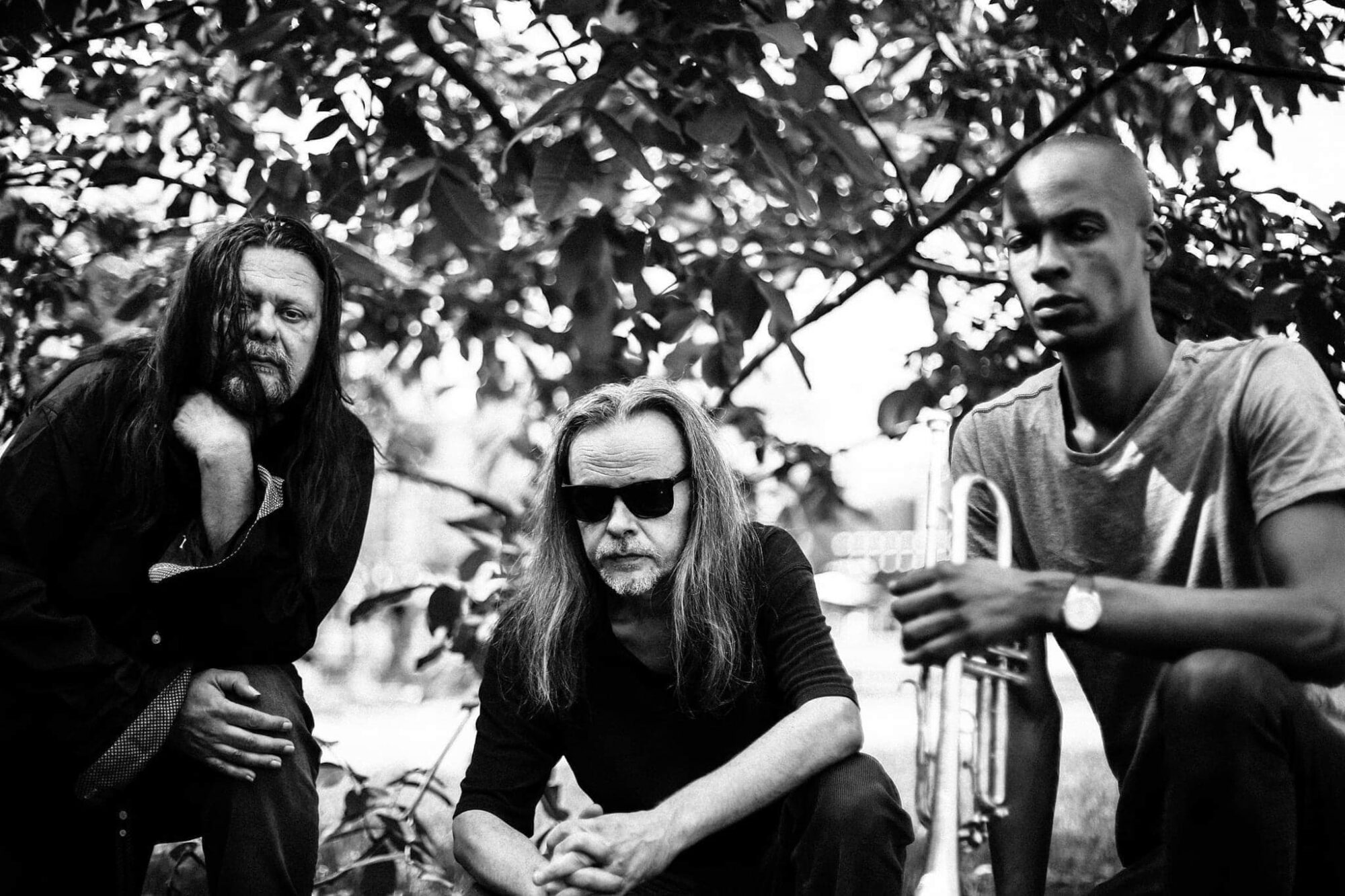Czarno-biała fotografia przedstawiająca trzech mężczyzn. Mężczyzna z prawej strony trzyma w dłoni trąbkę.