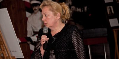 Zdjęcie przedstawia Ewę Soska podczas wernisażu. Artystka trzyma w ręce mikron.