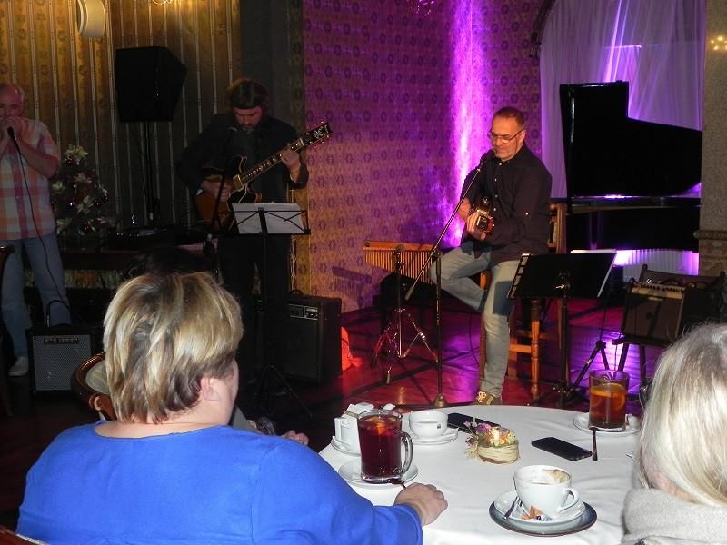 Zdjęcie przedstawia Eugeniusza Szwarcera grającego na gitarze w towarzystwie zespołu