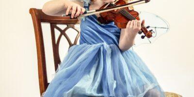 Zdjęcie przedstawia małą dziewczynkę grającą na skrzypcach