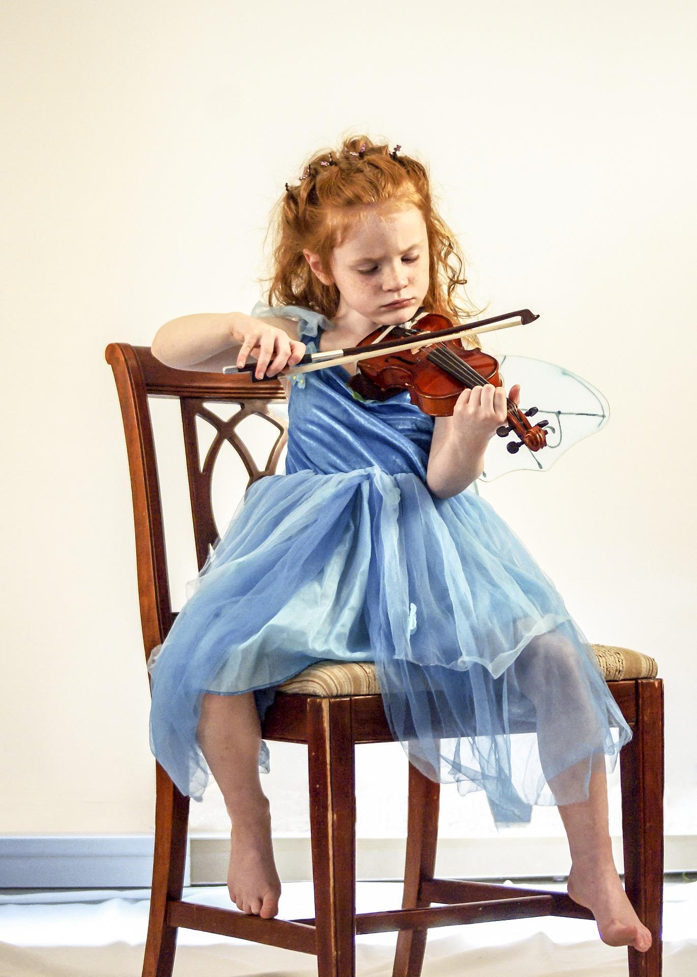 Mała dziewczynka o rudych włosach, ubrana w niebieską sukienkę grająca na skrzypcach.