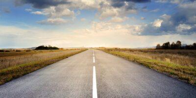 Pusta droga dwupasmowa, otoczona roślinnością. Niebieskie niebo otoczone szarymi chmurami.