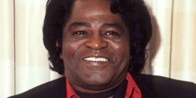 Uśmiechnięty czarnoskóry mężczyzna o średniej długości włosów w czerwonej koszuli i czarnym garniturze.