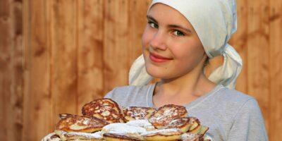Młoda dziewczyna w białej chuście na głowie, trzymająca talerz wypieków