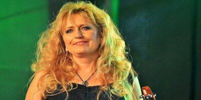 Uśmiechnięta kobieta o średniej długości włosach blond na zielonym tle. W prawym dolny rogu kawałek gryfu gitary,