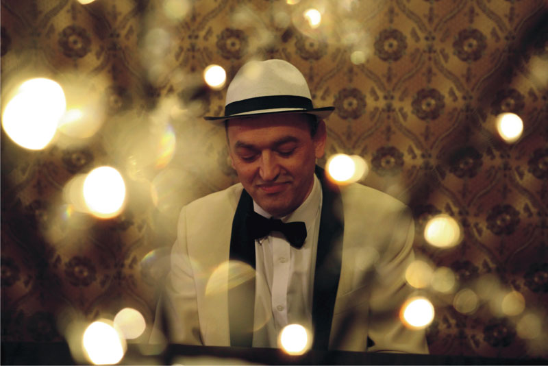 Bohdan Wantuła grający na fortepianie w Willi Fitznera, ubrany w biały garnitur oraz białą koszulę i czarną muchę. Na głowie ma biały kapelusz z czarną lamówką.