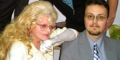 Prelegent Artur Bauc , ubrany w szary garnitur oraz błękitną koszulę i wzorzysty krawat wraz z piosenkarką - Violettą Villas, ubraną w kremową bluzkę. Na dłoniach artystki białe rękawiczki.