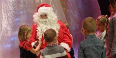 Grupa dzieci, stojąca przed postacią siedzącego na krześle św. Mikołaja – mężczyzny w czerwonym płaszczu, czerwonych spodniach i czerwonej czapce. Mężczyzna z siwo-białą długą brodą i wąsami, w okularach.