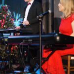 Katarzyna Wantuła w czerwonej sukni gra na organach. Obok Kamil Wantuła gra na wibrafonie.