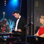 Katarzyna Wantuła w czerwonej sukni gra na organach. Obok Kamil Wantuła gra na wibrafonie. Oboje na scenie SCK- Bytków