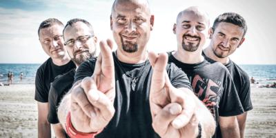Zdjęcie przedstawia członków zespołu Łydka Grubasa. Na pierwszym planie wokalista, bo jego bokach pozostali członkowie zespołu