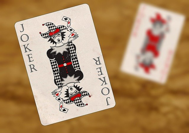 Na pierwszym planie duża karta Joker