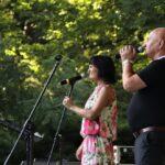 Na zdjęciu Piotr Herdzina i jego wokalistka śpiewają do mikrofonów. W tle zielone drzewa rosnące za płotem amfiteatru. Foto Monika Bilska
