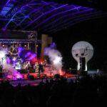 Na zdjęciu widok ogólny amfiteatru podczas koncertu Rock Noc. Widać scenę z kolorowymi światłami, na niej zespół oraz ciemne sylwetki fanów i biały balon SCK. Foto Monika Bilska