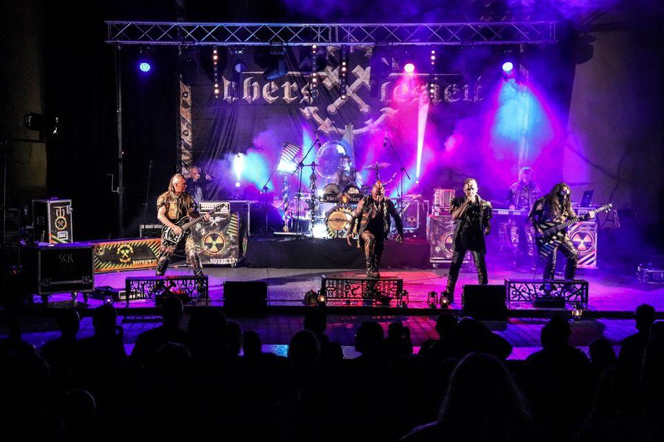 Na zdjęciu widok ogólny amfiteatru podczas koncertu Rock Noc. Widać scenę z kolorowymi światłami, na niej zespół oraz ciemne sylwetki fanów. Foto Monika Bilska