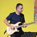 Na zdjęciu zbliżenie na postać znakomitego gitarzysty - Bohdana Lizonia. Muzyk gra na gitarze na tle żółtej ściany amfiteatru. Foto Monika Bilska