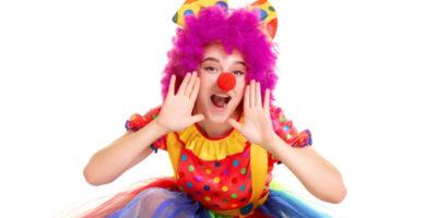Młoda dziewczyna przebrana za clowna na białym tle.