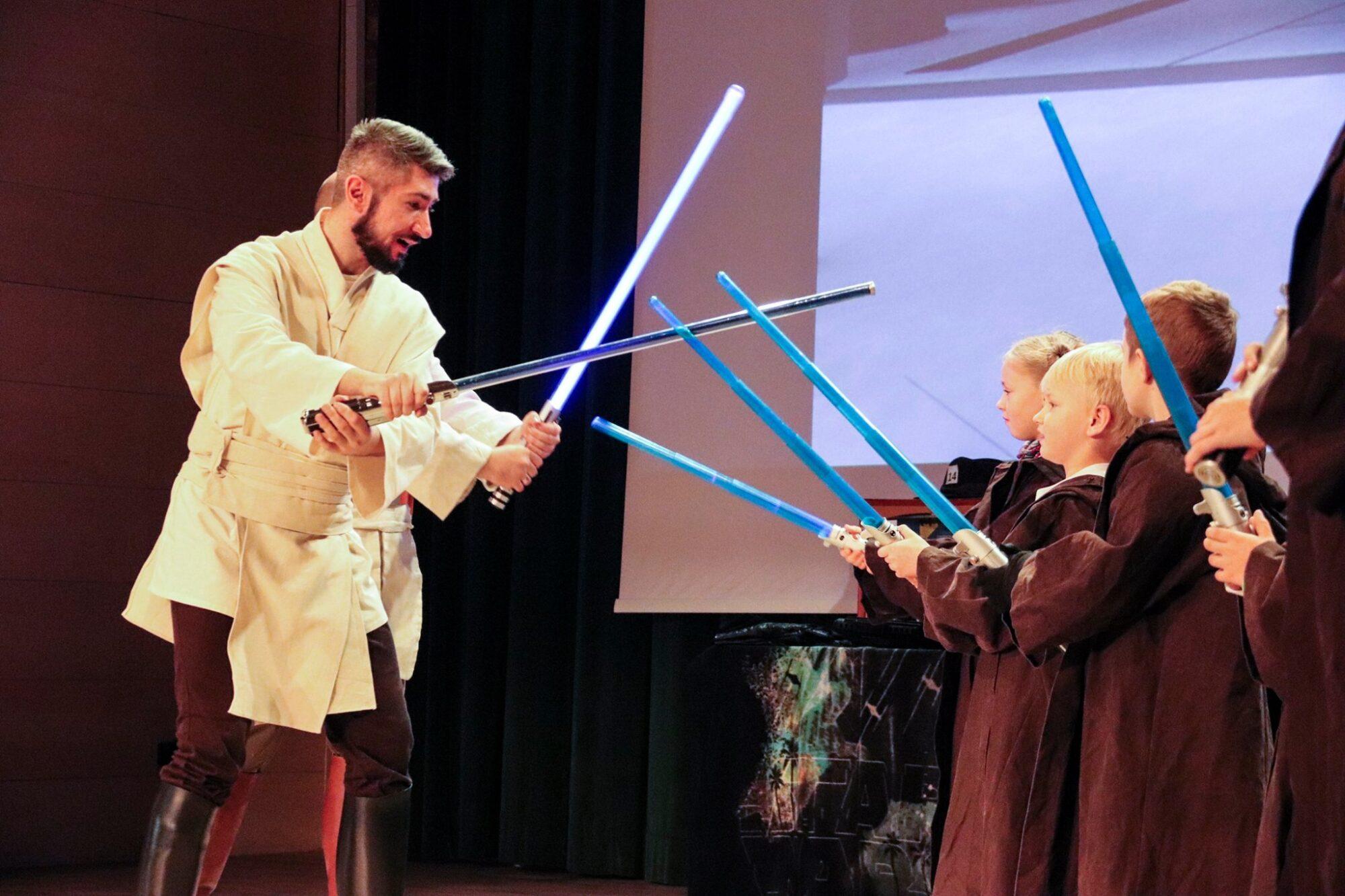 Po lewej stronie mężczyzna w białej bluzie i brązowych spodniach, po prawej grupa dzieci w brązowych długich okryciach Wszyscy trzymają niebieskie długie przedmioty przypominające miecze