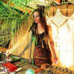 Kobieta stojąca przed mikrofonem, przed nią stół ze sprzętem DJ.