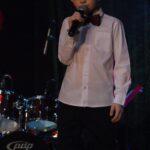 Szymon Wantuła w białej koszuli i muszce śpiewa do mikrofonu na scenie SCK- Bytków