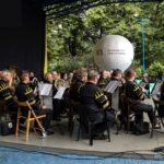 Widok boczny na siedzącą w strojach górniczych na scenie amfiteatru orkiestrę. W tle biały balon reklamowy SCK. Foto Monika Bilska
