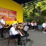 Widok boczny na siedzących na scenie muzyków orkiestry Siemion Band. W tle, na ścianie czerwony baner z napisem Koncerty Letnie.