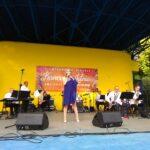 Widok na scenę amiteatru na któej w ramach Letnich Koncertów występują muzycy orkiestry Siemion Band. Towarzyszy im wokalistka Aleksandra Stano.