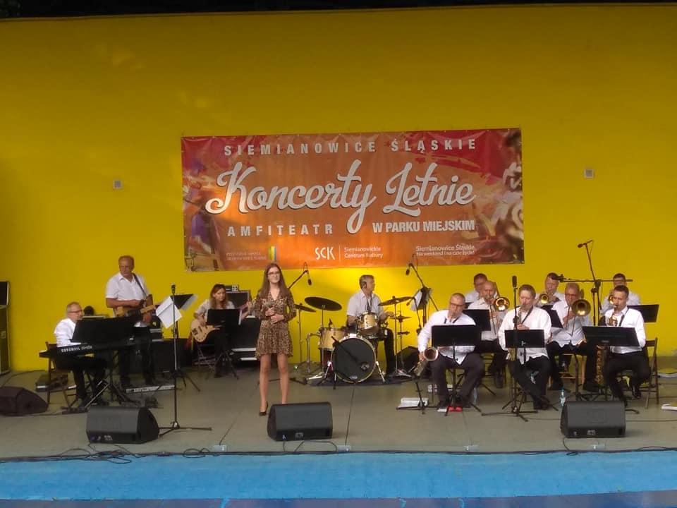 Widok na scenę amiteatru na któej w ramach Letnich Koncertów występują muzycy orkiestry Siemion Band. Towarzyszy im wokalistka Zuzanna Krupa.