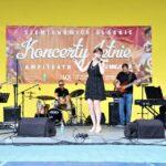 Widok ogólny na scenę amfiteatru na której znajdują wokalistka Kaja Karaplios oraz instrumentaliści. W tle czerwony baner reklamujący Letnie Koncerty. Foto Monika Bilska