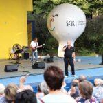 Widok ogólny na widownię pełną fanów oraz scenę amfiteatru. Na scenie Piotr Herdzina i jego zespół. Z boku stoi biały balon reklamowy SCK. Foto Monika Bilska