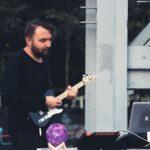 Zbliżenie na gitarzystę zespołu The Party is Over. Ubrany na czarno gra na swojej gitarze. Przed nim leży fioletowa kula, element dekoracji. Foto Monika Bilska