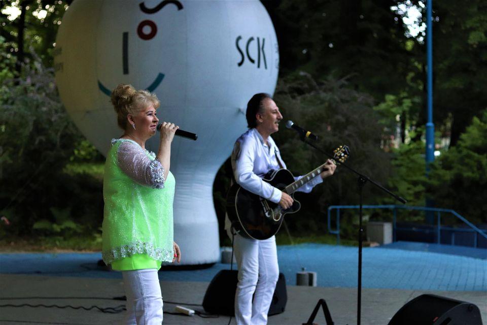 Zbliżenie na sylwetki muzyków zespołu Metrum. Teresa ma na sobie żóltą tunikę i białe spodnie. Ubrany na biało Marek Halup śpiewa i gra na gitarze. Foto Monika Bilska