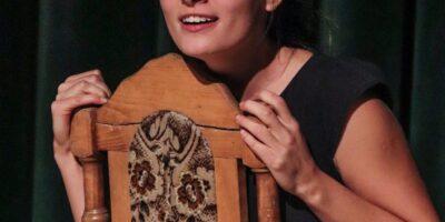 Zdjęcie przedstawia aktorkę odgrywającą rolę na scenie podczas spektaklu
